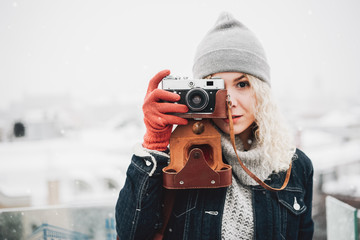 Blond curly girl with film photo camera, winter