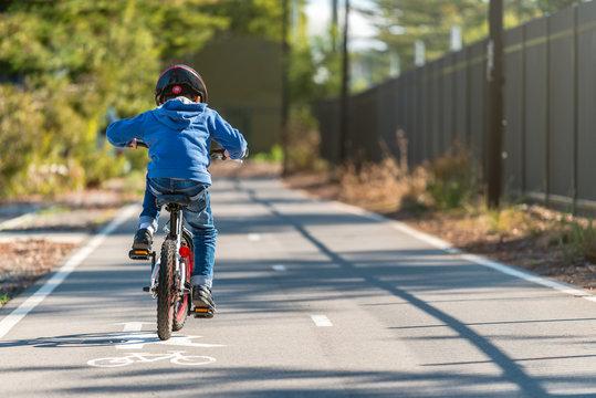Kid riding his bicycle on bike lane