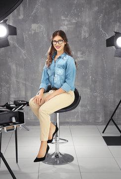 Beautiful young woman sitting on bar stool