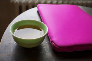 Cup with japanese green tea on the round table with notebook in the pink case