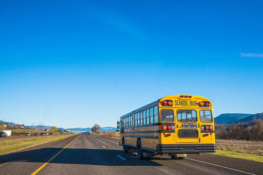 yellow school bus running on the road against the blue sky.