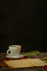 Cup of coffee, a book and autumn leaves on old boards