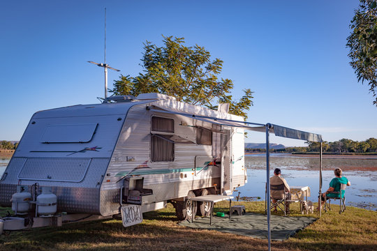 Retired couple with small dog sitting enjoying view to lake alongside modern caravan