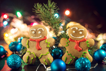 gingerbread man near Christmas tree with toys by garland