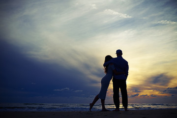 Silhouette of couple embracing while looking to the sunset