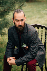 Portrait of a bearded groom sitting in a chair.