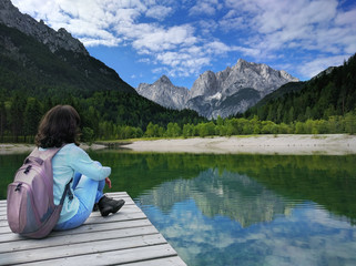 View of the Julian Alps with girl sitting on pier in Slovenia