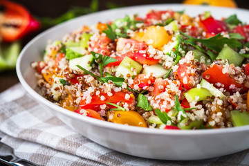 Fresh healthy salad with quinoa, colorful tomatoes, sweet pepper, cucumber and parsley on wooden background close up. Food and health. Superfood meal.