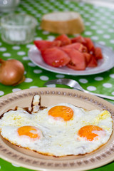 Fried eggs for breakfast with tomato in background