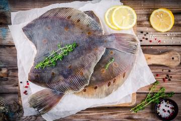 Raw flounder fish, flatfish on wooden table