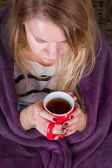 Girl sitting on sofa in livingroom with tea