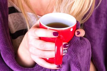 female hands holding mug of hot tea