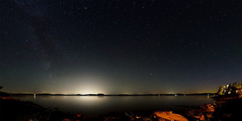 Panorama of the night sky above a lake in Sweden. The Milky Way is visible on the left and the bright light of large cities on the opposite side of the lake. In the foreground is the rocky coastline.