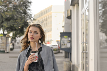 Girl goes on the sidewalk and drinking coffee