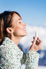 portrait d'une belle femme souriant qui applique du stick de protection solaire sur sa bouche