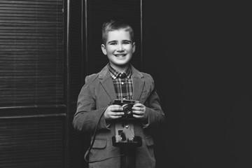 Handsome young boy with retro camera