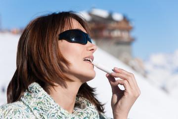 portrait d'une femme qui met de l'écran total sur ses lèvres