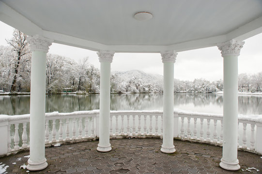 building with roof and columns on background of winter landscape with lake