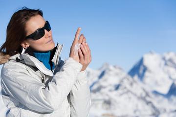 portrait d'une femme se mettant de la crème sur les mains en hiver à la neige