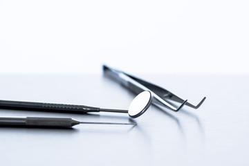 A dentist's tools (mirror, tweezers, probe)