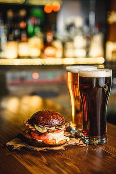 Hamburger and dark light beer on a pub background.