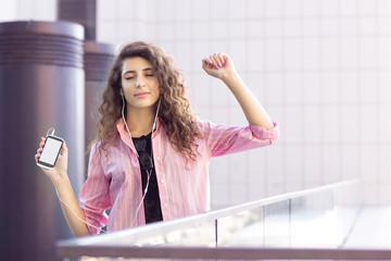 Curly girl enjoys music, closed eyes
