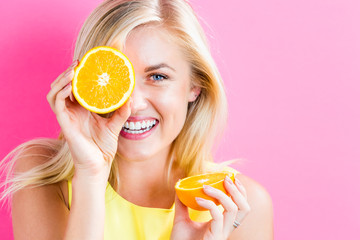 Happy young woman holding orange halves