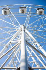 Underside view of a white ferris wheel on blue sky background