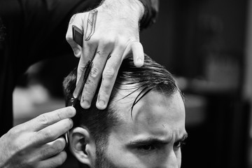 Hand cut with scissors the man in the barbershop close-up, black-and-white photo