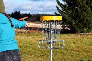 Young woman throwing disc to target on disc golf course.