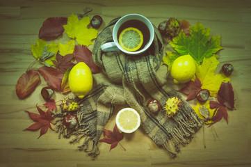 Tasse Tee mit Schal / Tasse Tee mit Zitronenscheibe, Schal und Herbstlaub mehrere Objekte in der Draufsicht fotografiert.