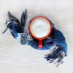 warming drink for the winter holidays/ frothy cappuccino in the red circle wrapped in a blue scarf