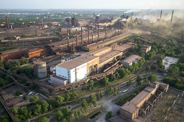 Industrial landscape in Ukraine. Steel factory with smog at sunset. Pipes with smoke. Metallurgical plant. steelworks, iron works. Heavy industry. Ecology problems, atmospheric pollutants.