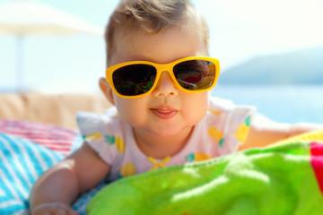 Smiling baby girl, wearing yellow sunglasses, sunbathing on the beach.