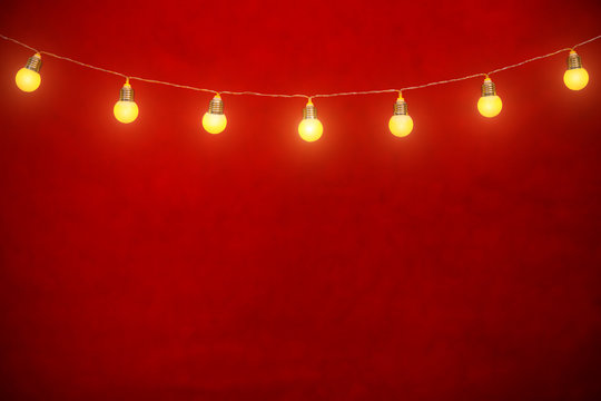 Hanging bulbs on rope with red background