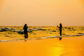 Silhouette photo. people taking picture on the beach at sea and sunset