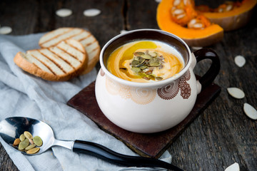 Creamy pumpkin cream soup with pumpkin sunflower seeds and olive oil