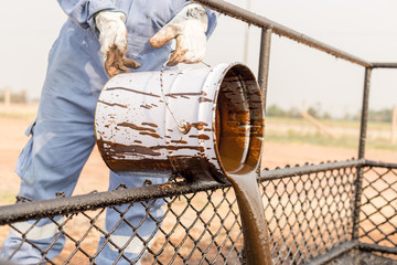 worker pouring crude oil from bucket. waste management