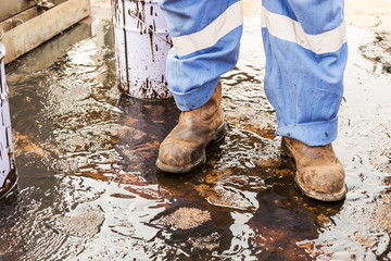 close up safety boot. worker cleaning crude oil contaminated on floor. waste management