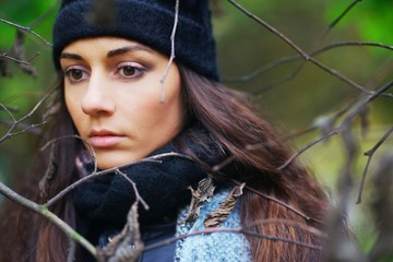 Beautiful pensive woman with brown eyes wearing a scarf and a hat in the Park among the bare branches of trees, closeup.