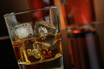 close-up of whiskey with ice cubes in glass near bottle on black background, warm atmosphere