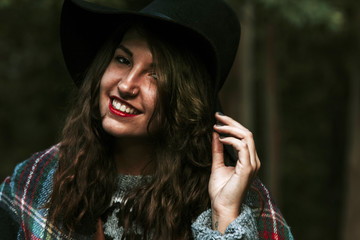 portrait of young woman with hat in the woods