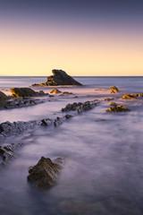 Rocks in a blue ocean in the morning.