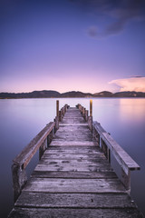 Wooden pier or jetty on a blue lake sunset. Italy