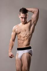 young bodybuilder posing studio, strong muscular