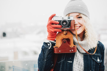 Smiling curly blond girl with retro film camera