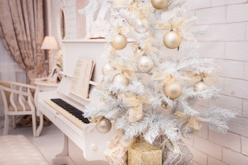 White Christmas tree decorated with golden winter ornament at the piano background.