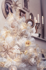 White Christmas tree decorated with rustic hand made ornaments, baubles, balls, flowers. Burning candles and vintage pictures as winter holiday background. Close-up