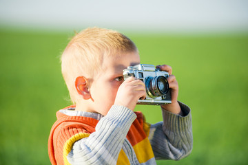 Little boy with an old camera shooting outdoor. Kid taking a photo using a vintage retro film cam. Green summer field.