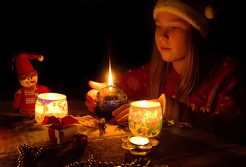 The girl on a dark background looking at a fading candle, festive background